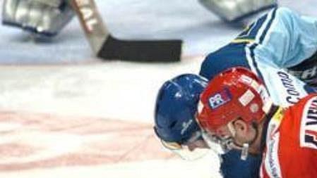 Tomáš Divíšek ze Slavie bojuje o puk s jedním ze vsetínských hokejistů.