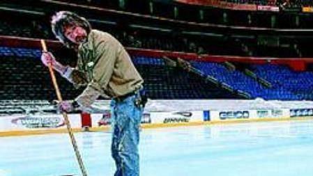 Pracovník Rochesteru připravuje ledovou plochu pro hokejový zápas.