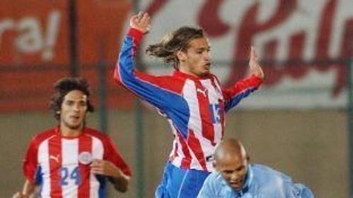 Paraguayský fotbalista Carlos Paredes (uprostřed) bojuje omíč sRubenem Oliverou zUruguaye.