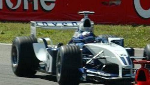 Němec Michael Schumacher ze stáje Ferrari před Kolumbijcem Juanem Pablem Montoyou zWilliamsu na trati Velké ceny Itálie vMonze.