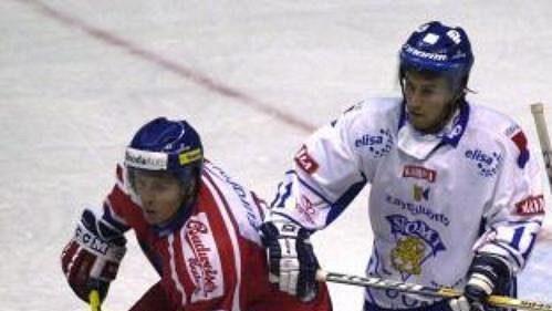 Fin Tony Virta mezi Jaroslavem Balaštíkem (vlevo) a brankářem Romanem Málkem během utkání, vněmž čeští hokejisté prohráli 1:3.