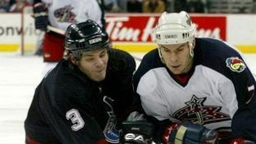 Brent Sopel zVancouveru (vlevo) blokuje Scotta Lachanca zColumbusu.