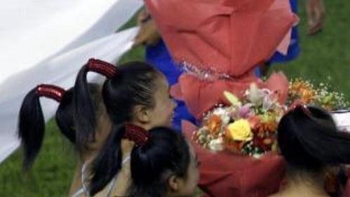 David Beckham je obklopen čínskými dívkami, které 2.srpna vPekingu na hrací ploše přivítaly hráče Realu Madrid před utkáním svýběrem Číny.