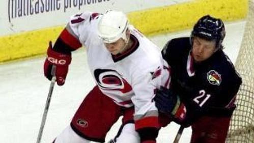 Hráč Caroliny Tomáš Malec (v bílém dresu) ohrožuje branku Columbusu, již hájí Marc Denis. Stíhá ho Espen Knutsen.