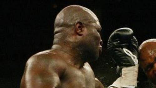 Evander Holyfield (vpravo) inkasuje od James Toneyho levý hák.