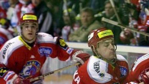 Třinecký hráč Libor Procházka se snaží zastavit Petra Koukala zPardubic (vpravo).