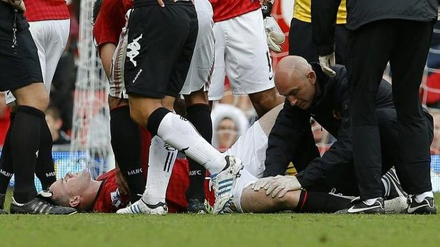 Wayne Rooney leží v bolestech na trávníku.