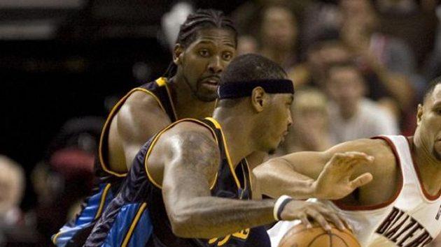 Basketbalista Denveru Carmelo Anthony (vlevo) proniká kolem hráče Portlandu Brandona Roye.