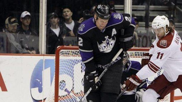 Hokejista Phoenixu Martin Hanzal (č. 11) napadá obránce Los Angeles Matta Greena.