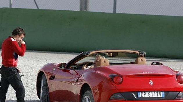 Fernando Alonso (vlevo) a Felipe Massa si prohlížejí zapadlé auto.