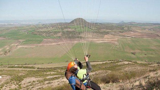 Paraglidista Jan Škrabálek krotí svůj padák na vrcholu Raná u Loun.