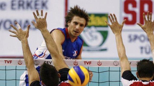 Francouzský volejbalista Antonin Rouzier (v modrém) smečuje přes blokující hráče Španělska.