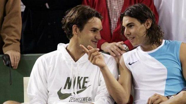 Tenisté Roger Federer (vlevo) a Rafael Nadal diskutují po vzájemné exhibici na hřišti s kombinovaným povrchem.