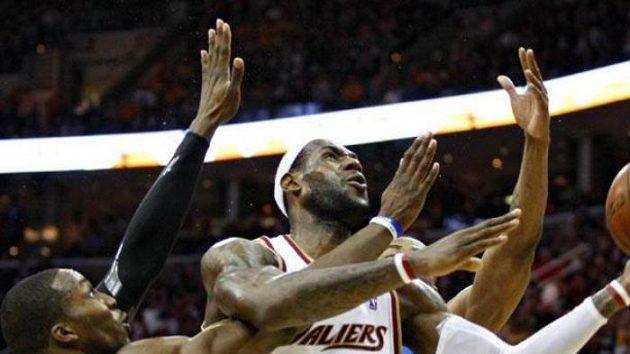 Basketbalista Clevelandu LeBron James (s míčem) zakončuje přes Dwighta Howarda z Orlanda ve finále Východní konference NBA.