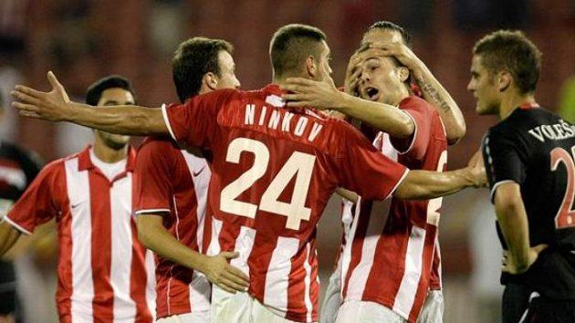 Slávista Ladislav Volešák přihlíží radosti fotbalistů CZ Bělehrad z gólu Slavka Peroviče.