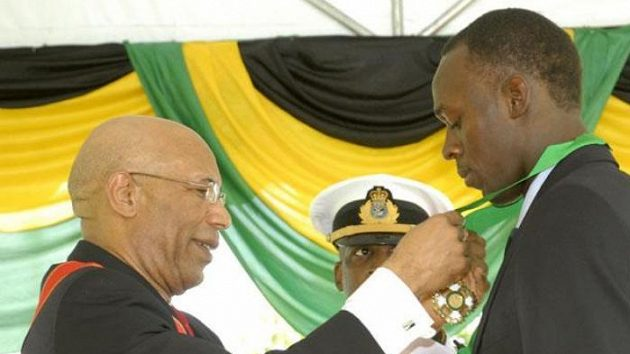Sprinter Usain Bolt přebírá jamajské státní vyznamenání od guvernéra Patricka Allena.