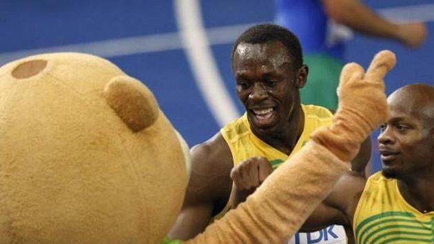Jamajští sprinteři Usain Bolt (uprostřed) a Asafa Powell oslavují s maskotem berlínského MS vítězství ve štafetě na 4x100 metrů.