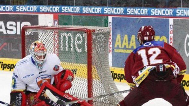 Finský brankář v barvách Chomutova Jan Lundell zasahuje proti střele sparťanského hráče.