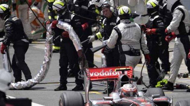 Mechanici odnášejí utrženou palivovou hadici z Kovalainenova vozu