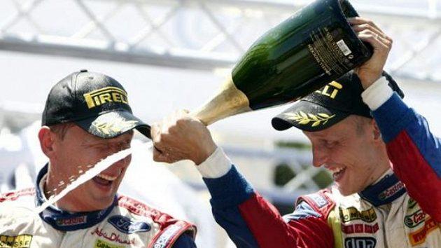 Finský pilot Mikko Hirvonen (vpravo) oslavuje se spolujezdcem Jarmo Lehtihenem vítězství. Teď už ví, že ani čtyři vyhrané soutěže na titul mistra světa nestačí.