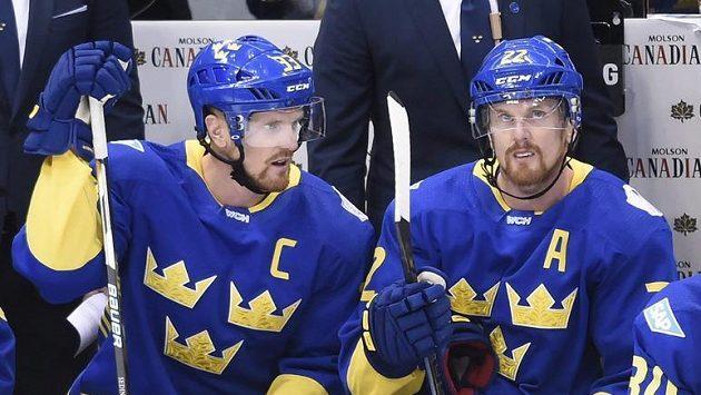 Henrik Sedin (vlevo) v debatě s Danielem Sedinem na švédské střídačce.