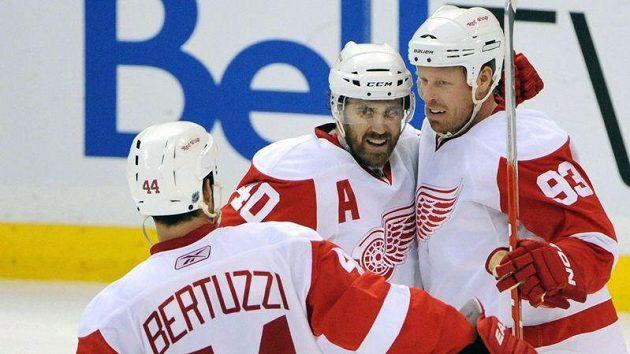 Todd Bertuzzi (vlevo) a Henrik Zetterberg (vpravo) gratulují svému spoluhráči z Detroitu Johanu Franzénovi k brance.