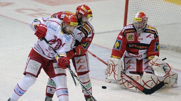 Petr Jelínek ze Slavie (uprostřed) brání třineckého kapitána Radka Bonka, který se snaží tečovat puk před gólmanem Pražanů Miroslavem Kopřivou.