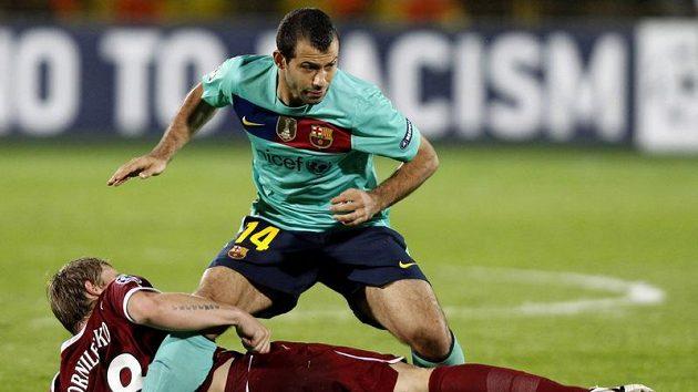 Javier Mascherano z Barcelony se pokouší obejít kazaňského hráče Sergeje Kornilenka (ležící).
