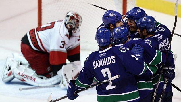 Hokejisté Vancouveru oslavují vstřelený gól, vlevo se zklamaně sbírá z ledu gólman Caroliny Cam Ward.