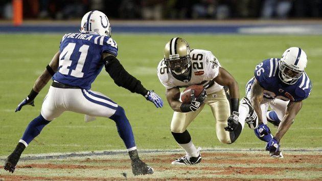 Reggie Bush z New Orleans se snaží projít mezi hráči Indianapolis Betheou (vlevo) a Haydenem