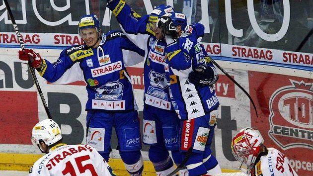 Hokejisté Komety Brno se radují z branky do slávistické sítě.