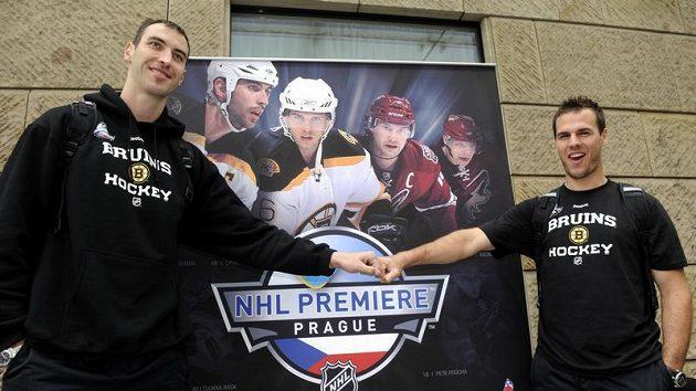 Hokejisté Boston Bruins Zdeno Chára (vlevo) a David Krejčí pózují před plakátem po příletu do Prahy.