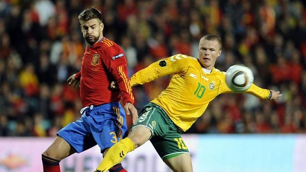 Litevec Darvydas Sernas (vpravo) v souboji o míč s Gerardem Piquém ze Španělska.