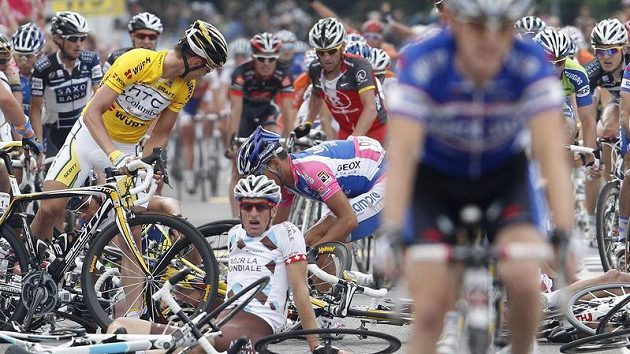 Lídr závodu Kolem Švýcarska Tony Martin (ve žlutém trikotu) kontroluje následky hormadného pádu v závěru čtvrté etapy.