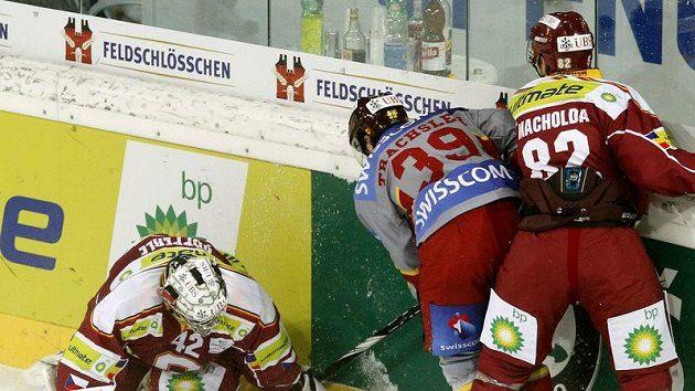 Brankář Sparty Tomáš Pöpperle kryje puk před Trachslerem z Ženevy