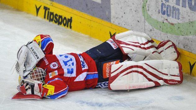 Brankář Pardubic Dominik Hašek leží na ledě po zákroku Martina Ručinského ze Sparty.
