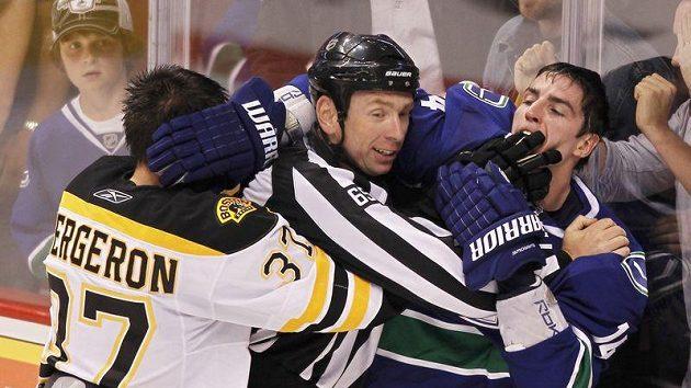 Centr Bostonu Bruins Patrice Bergeron se přetlačuje s Alexem Burrowsem z Vancouveru.