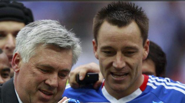 Kouč Carlo Ancelotti (vlevo) s pohárem za vítězství v FA Cupu. Ve Wembley bude usilovat o třetí trofej.