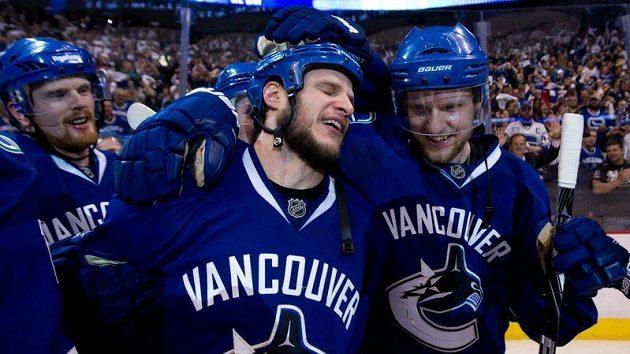 Zleva Daniel Sedin, Kevin Bieksa a Alexander Edler z Vancouveru se radují po vítězství nad Žraloky.