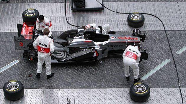 Mechanici McLarenu kompletují monopost MP4-26 při slavnostní prezentaci v Berlíně.