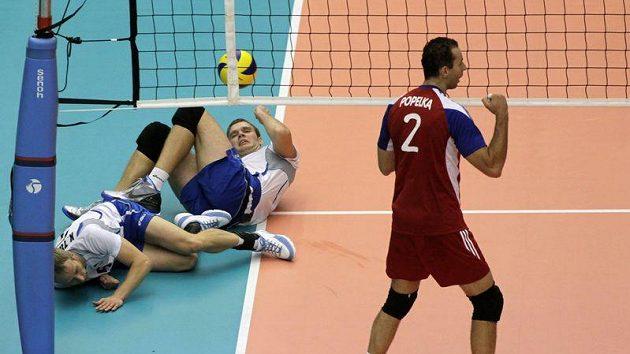Český volejbalista Jiří Popelka (vpravo) se raduje, zatímco Estonci Kert Toobal (vlevo) a Oliver Venno leží na zemi.