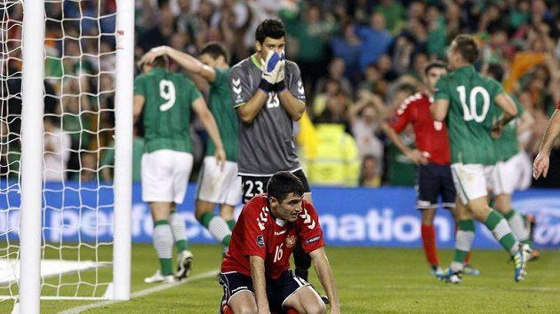Arménský zoufalec Valerij Aleksanjan reaguje za asistence brankáře Arsena Petrosjana na vlastní gól, kterým poslal Irsko do vedení...