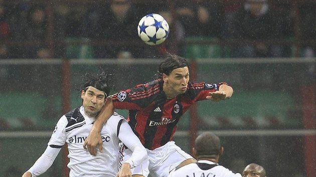 Zlatan Ibrahimovic z AC Milán (uprostřed) se snaží prosadit přes Vedrana Corluku z Tottenhamu.