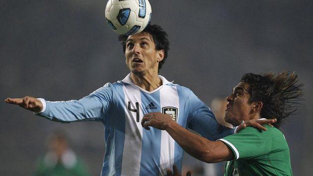 Nicolas Burdisso z Argentiny (vlevo) bojuje o míč s Marcelem Morenem z Bolívie.