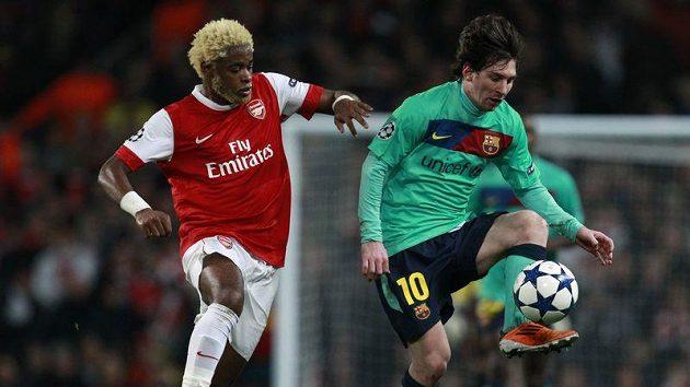 Lionel Messi (vpravo) zpracovává míč před Alexem Songem z Arsenalu
