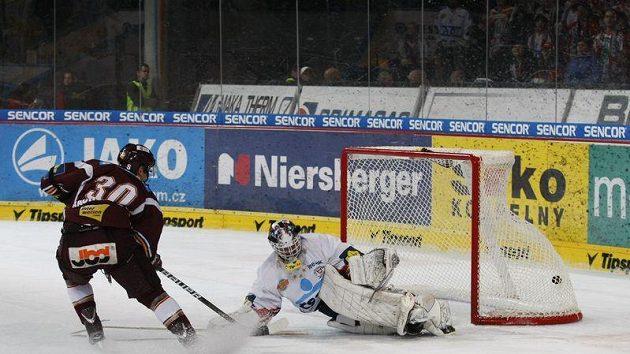 Útočník Sparty Tomáš Rachůnek střílí gól pardubickému brankáři Martinu Růžičkovi.