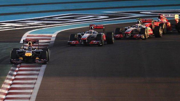 Sebastian Vettel (vlevo) vyjíždí po startu závodu v Abú Zabí z první zatáčky. Vzápětí přišel o tlak v pravé zadní pneumatice.