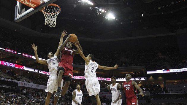 LeBron James z Miami (uprostřed) se prosazuje mezi dvojicí hráčů Charlotte.