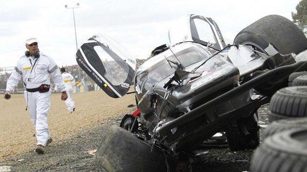 Bezpečnostní pracovník si prohlíží vrak Audi R18 TDI britského pilota Allana Mcnishe.
