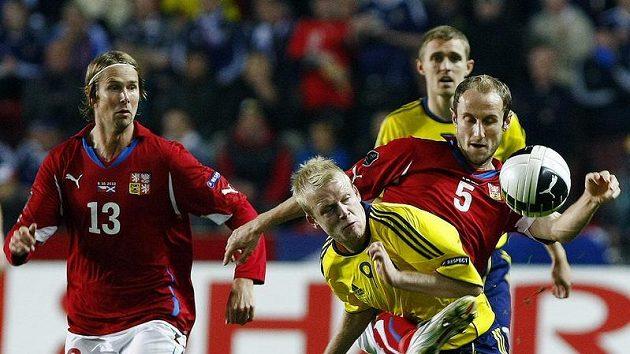 Roman Hubník (vpravo v červeném) nekompromisně bojuje o míč se skotským útočníkem Naismithem.